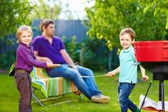 Lyckliga ungar som slåss med kökobjekt på picknick Royaltyfria Foton