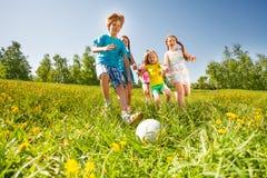 Lyckliga ungar som spelar fotboll i grönt fält Royaltyfria Bilder