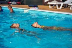 Lyckliga ungar som spelar i blått vatten av simbassängen Arkivfoto