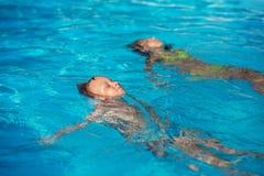 Lyckliga ungar som spelar i blått vatten av simbassängen Fotografering för Bildbyråer