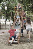 Lyckliga ungar som spelar i lekplats Royaltyfri Foto