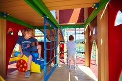 Lyckliga ungar som spelar lekar på färgrik slottlekplats Arkivfoton