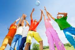 Lyckliga ungar som spelar med bollbanhoppning i luft Fotografering för Bildbyråer