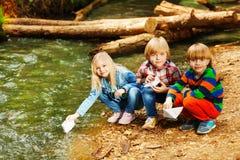 Lyckliga ungar som spelar med pappers- fartyg på flodbanken Arkivfoton
