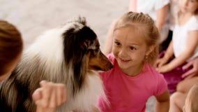 Lyckliga ungar som spelar med terapihunden stock video