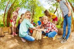 Lyckliga ungar som spelar med trä, loggar in skogen Arkivbilder