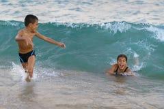 Lyckliga ungar som spelar på havet Royaltyfria Bilder