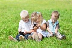 Lyckliga ungar som spelar på smartphones Arkivbild