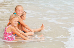 Lyckliga ungar som spelar på stranden Royaltyfria Foton