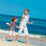 Lyckliga ungar som spelar på stranden Arkivbild