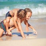 Lyckliga ungar som spelar på stranden på dagtiden Arkivfoto