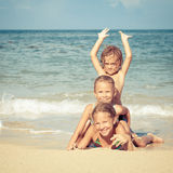 Lyckliga ungar som spelar på stranden på dagtiden Arkivfoton