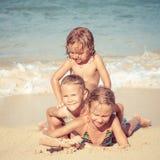 Lyckliga ungar som spelar på stranden på dagtiden Royaltyfri Foto