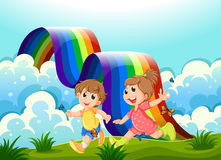 Lyckliga ungar som spelar på bergstoppet med en regnbåge Royaltyfri Fotografi