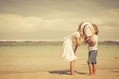 Lyckliga ungar som spelar på stranden Royaltyfria Bilder