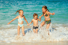 Lyckliga ungar som spelar på stranden Arkivbilder
