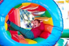 Lyckliga ungar som spelar på uppblåsbar dragningslekplats Royaltyfria Bilder