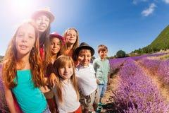 Lyckliga ungar som står i lavendelfält på den soliga dagen Arkivfoto