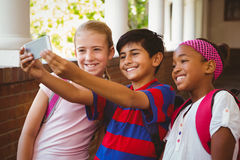 Lyckliga ungar som tar selfie i skolakorridor Royaltyfri Fotografi
