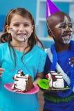Lyckliga ungar som äter födelsedagkakan Arkivfoto
