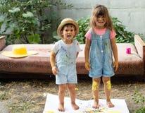 Lyckliga ungar som tillsammans gör konsthantverk Stående av den förtjusande lilla flickan och pojken som lyckligt ler, medan tyck royaltyfri bild