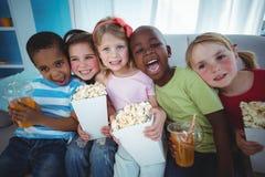 Lyckliga ungar som tycker om popcorn och drinkar, medan sitta Royaltyfri Bild