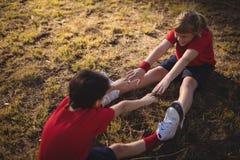 Lyckliga ungar som utför sträcka övning under hinderkurs royaltyfria bilder