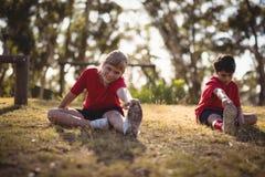 Lyckliga ungar som utför sträcka övning under hinderkurs royaltyfri fotografi