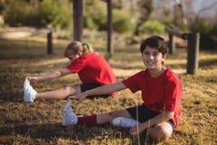 Lyckliga ungar som utför sträcka övning under hinderkurs royaltyfri foto