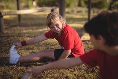 Lyckliga ungar som utför sträcka övning under hinderkurs royaltyfri bild