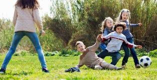 Lyckliga ungar som utomhus spelar fotboll Royaltyfri Foto