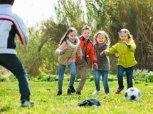 Lyckliga ungar som utomhus spelar fotboll Arkivbild