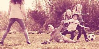 Lyckliga ungar som utomhus spelar fotboll Fotografering för Bildbyråer