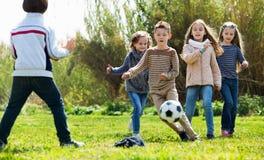 Lyckliga ungar som utomhus spelar fotboll Arkivbilder