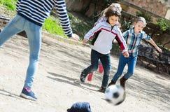 Lyckliga ungar som utomhus spelar gatafotboll arkivbilder
