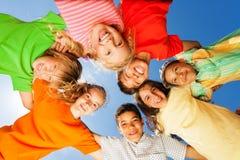 Lyckliga ungar stänger sig i cirkel på himmelbakgrund Royaltyfria Foton