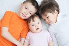 Lyckliga ungar, tre skratta olika åldrar för barn som ligger, ståenden av pojken, liten flicka och behandla som ett barn flickan, Royaltyfri Foto