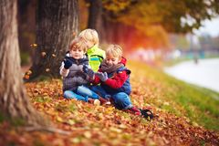 Lyckliga ungar, vänner som har gyckel bland stupade sidor i höst, parkerar arkivfoto