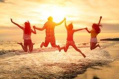 lyckliga ungdomarsom hoppar på stranden Royaltyfria Foton