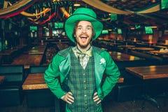 Lyckliga upphetsade hållhänder för ung man på höfter och leende till kameran Han bär Sts Patrick dräkt Grabbställning bara i bar royaltyfria foton