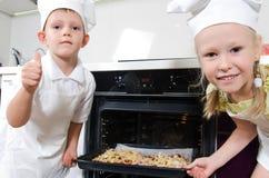 Lyckliga upphetsade unga barn med hemlagad pizza Royaltyfria Bilder