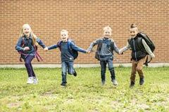 Lyckliga upphetsade ungar som har gyckel tillsammans på lekplats royaltyfria bilder