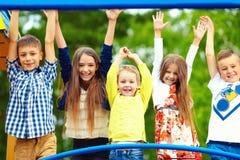 Lyckliga upphetsade ungar som har gyckel tillsammans på lekplats arkivfoto