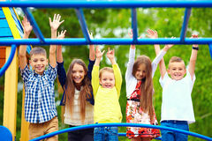 Lyckliga upphetsade ungar som har gyckel tillsammans på lekplats arkivfoton
