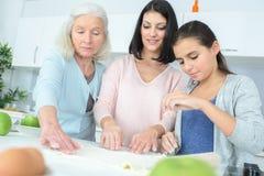 Lyckliga utvecklingar för familj som tre tillsammans lagar mat Royaltyfri Foto