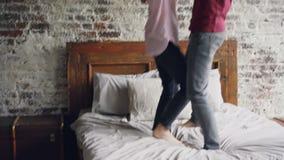 Lyckliga vänner dansar på sänginnehavhänder och tycker om gift liv tillsammans Modern dubbelsäng, tegelstenvägg och arkivfilmer