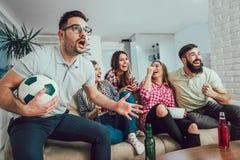 Lyckliga vänner eller fotbollsfan som håller ögonen på fotboll på tv arkivfoto