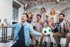 Lyckliga vänner eller fotbollsfan som håller ögonen på fotboll på tv royaltyfri bild