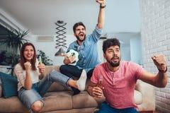 Lyckliga vänner eller fotbollsfan som håller ögonen på fotboll på tv och firar seger royaltyfri bild