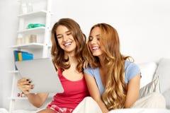 Lyckliga vänner eller tonåriga flickor med minnestavlaPC hemma royaltyfria bilder